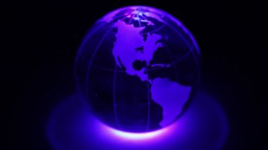Glass Earth sphere spins and ring of color light below it — Stock Video