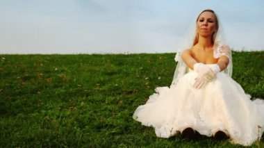 Bride in white dress sits one on grass on hill slope — Stock Video