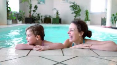 Little girl with her mother stay on edge of indoor pool — Stock Video