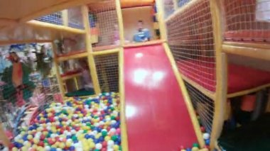 Children play ballpool filled with multi-colored spheres — Stock Video