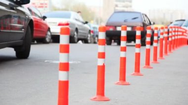 Protective barrier made of striped columns, in defocus people and cars — Stock Video