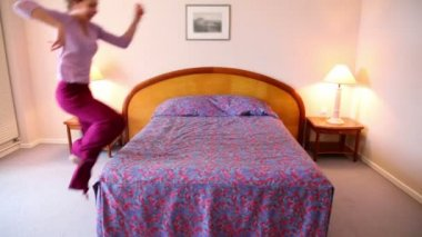 Young woman runs and jumps on bed then lies on it — Stock Video