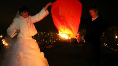 Newly-married couple sets fire to heavenly small lamp in city — Stock Video