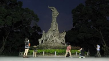 Tourists are photograph near to Sculpture of Five Rams in night — Stock Video