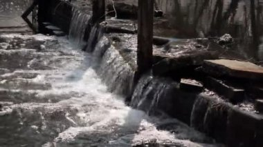 Water flow over big stones on dam in river — Stock Video