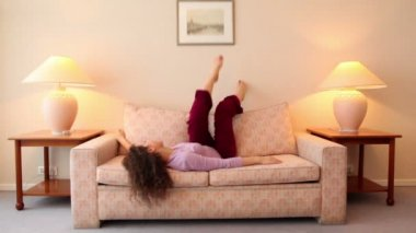 Young woman lies on sofa and shake legs at room with lamps on each side — Stock Video