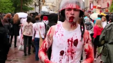 Bloody zombie soldier in helm walk by street among people during Zombie Parade — Stock Video