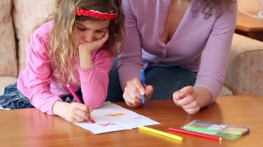 Mother with daughter sit on sofa at wooden table and draw with markers — 图库视频影像