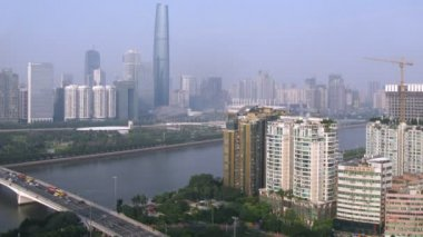 Zhujiang New Town stands on opposite to river bank to which cars on bridge go — Stock Video