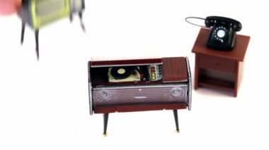 Fingers takes toy vintage phonograph, phone and tv set — Stock Video