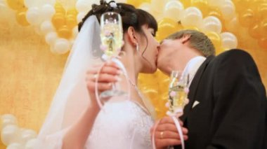 Newly-married couple kisses champagne glasses in hands against wall — Stock Video