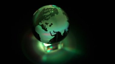 Toy Earth sphere stand on cube with color illumination, composition spins — Stock Video
