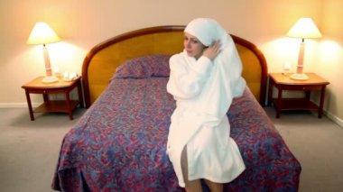 Kvinnan i vit morgonrock kommer till sovrum och torka håret med handduk — Stockvideo