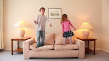 Two kids jump on sofa at room with lamps on each side — Stock Video