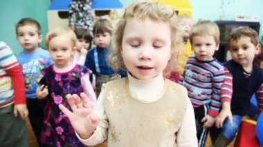 Nice girl and other kids carefully look into camera in a Moscow kindergarten 143 — Stock Video