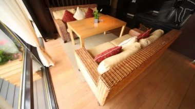 Wicker sofa stand in restaurant lounge fenced from of terrace by glass door with hangings — Stock Video