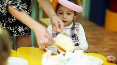 Child-minder lays out pieces of cake to kids sitting at table in kindergarten — Stock Video