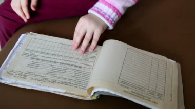 Little girl turns over pages of medical chart — Стоковое видео