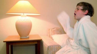 Little boy in white bathrobe sit and yawns before lay to sleep on bed — Stock Video