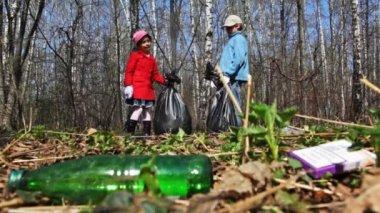 Kardeş elinde çanta çöp park toplamak — Stok video