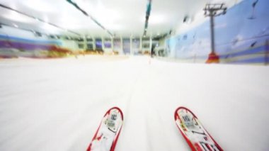 Close-up of skis fast going down hill in big sport center perambulate barriers — Stock Video