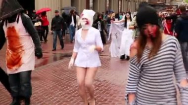 Zombie nurse walk along street in bloody bandage during Zombie Parade — Stock Video