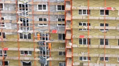 Workers stands on scaffold put window frame and glaze windows — Stock Video