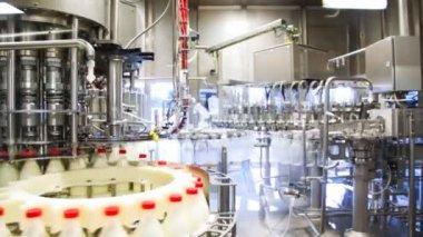 Wiele pustych butelek, umyte i lewo pojawiają się już pełne mleko w ogromnej fabryki, szeroki widok — Wideo stockowe