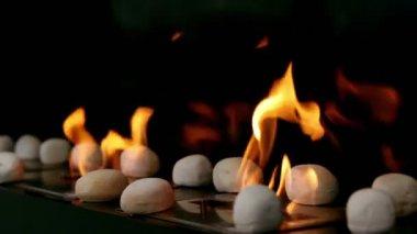 Jazyky plamenů projít otvoru v plechu s kameny na něm — Stock video