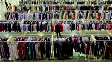 Several women watch goods among lot of clothes in shop — Stock Video