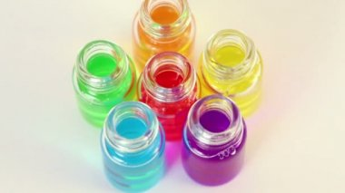 Six transparent open bottles rotates with color oil on them — Stock Video