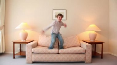 Little boy jumps on sofa at room with lamps on each side — Stock Video