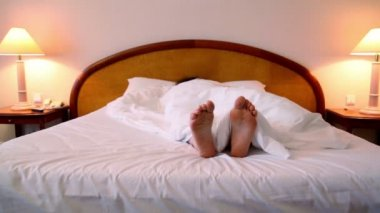 Woman lay in bed under blanket and moves bootless feet — Stock Video