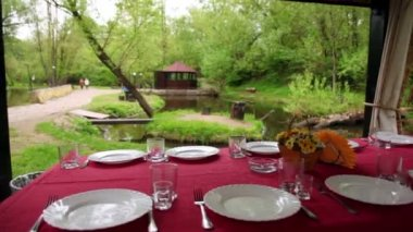 Dining table is set in bower ashore of small pond at among trees at summer — Stock Video