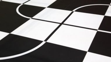 Two robot toy cars moves along intersecting lines drawn on chessboard — Stock Video