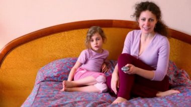 Madre e hija sentarseen en la cama y ver la televisión con control remoto — Vídeo de Stock