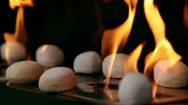 Tongen van vuur gaan door groef in metalen plaat met stenen op het — Stockvideo