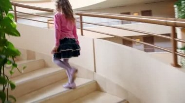 Little girl walks upstairs by circular staircase in multiple floor building — Stock Video