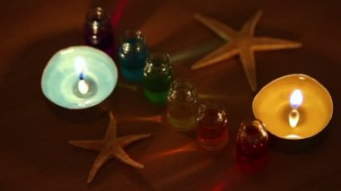 Two candles burn, six open bottles with color aroma oil and sea star lay — Stock Video