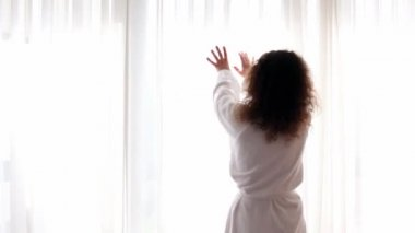 Woman comes to draws curtains and walks away, street traffic outside window — Stock Video