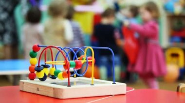 Close-up conundrum toy standing on table, in defocus behind it children play — Stock Video