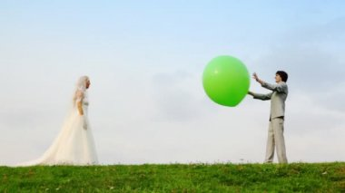 Newly married play meadow with each other inflatable sphere — Stock Video