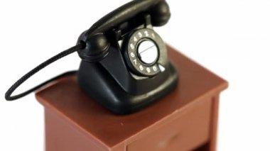 Zwarte speelgoed telefoon op kleine tafel draaiingen geïsoleerd — Stockvideo