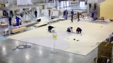 Several workers make floor and other build house in exhibition hangar — Stock Video