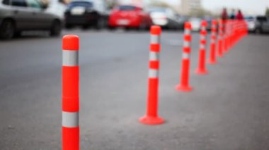 Protective barrier made of striped columns, people and cars go road — Stock Video
