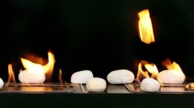 Tongues of flame go through two slots in metal plates with stones on it — Stockvideo