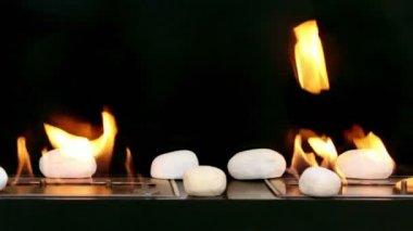 Tongen van vuur gaan door middel van twee sleuven in metalen platen met stenen op het — Stockvideo