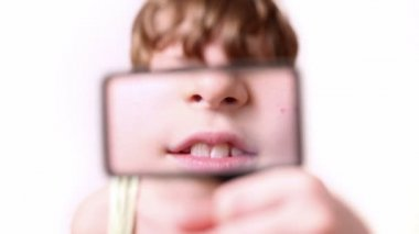 Little boy moves rectangular magnifying glass in front of his face — Stock Video