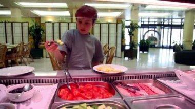 Pojken tar mat och lägga den på plattan i restaurang — Stockvideo