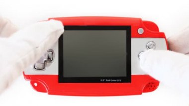 Hands in white gloves click on buttons portable game console — Stock Video